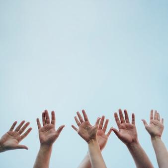 Várias mãos levantadas no ar