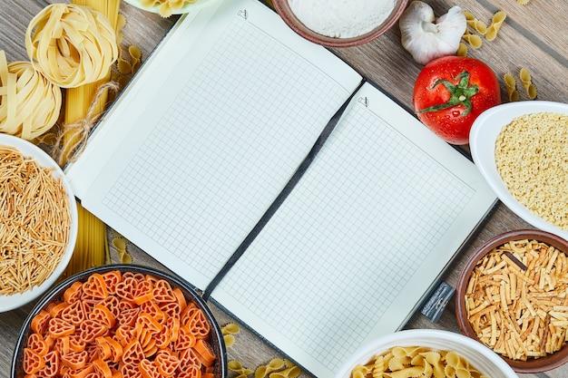 Várias massas alimentícias não cozidas com caderno e legumes em uma mesa de madeira.