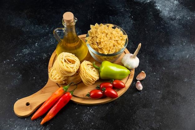 Várias massas, óleo e vegetais na placa de madeira.