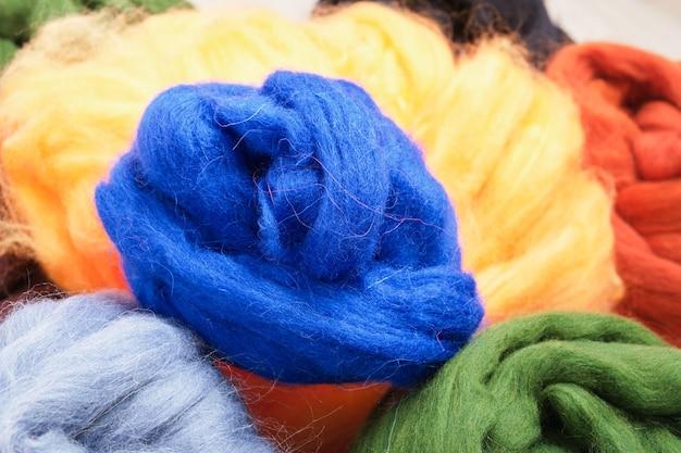 Várias meadas de lã de ovelha tingida natural para feltragem em close-up da mesa