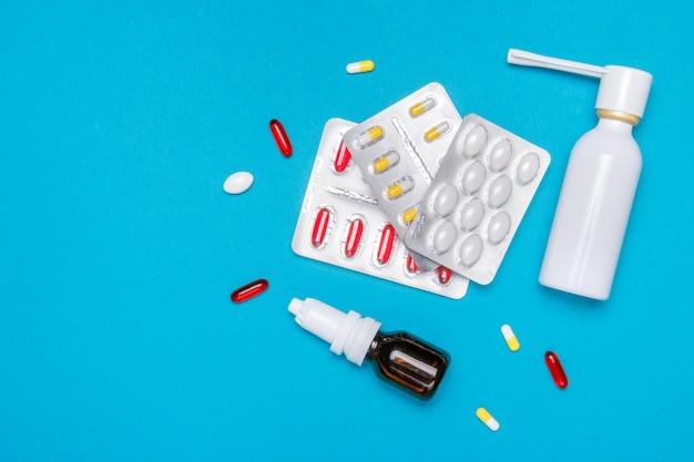 Várias medicinas, sprays de um nariz entupido e uma dor em uma garganta em um fundo azul.