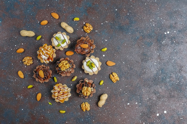 Várias mini tortinhas caseiras com nozes e creme de chocolate.