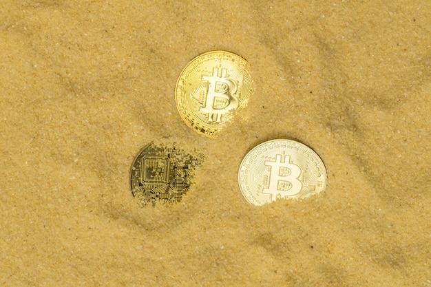 Várias moedas criptográficas bitcoin em areia dourada brilhante, vista superior. encontrar e minerar criptomoeda