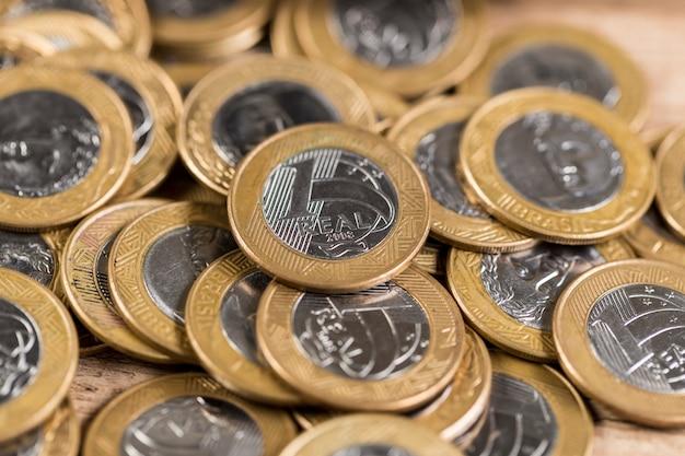 Várias moedas de 1 real em uma mesa de madeira