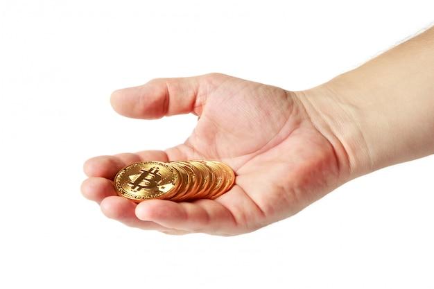 Várias moedas de ouro com um sinal de bitcoin estão na palma da mão de um homem em um fundo branco