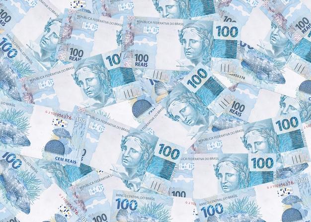 Várias notas de cem reais do brasil, textura de dinheiro brasileiro, notas de superfície de reais Foto Premium