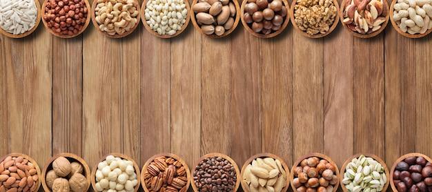 Várias nozes e sementes na mesa de madeira com espaço de cópia