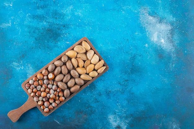 Várias nozes em uma placa, na mesa azul.