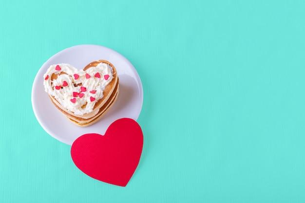 Várias panquecas caseiras em forma de coração cobertas com creme com doces coloridos em um prato branco e um cartão de coração vermelho em branco sobre um fundo azul brilhante, copie o espaço. conceito de café da manhã do dia dos namorados