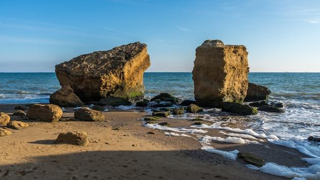 Várias pedras enormes calcárias à beira-mar