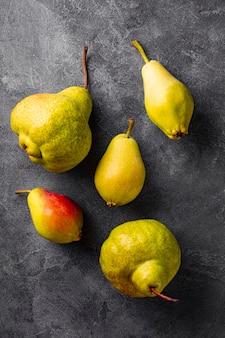 Várias peras maduras em fundo cinza, vista superior, foto vertical de frutas feias com tendências