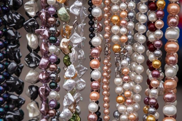 Várias pérolas coloridas no mercado. fundo de um colar colorido feito de pedras preciosas e miçangas coloridas.