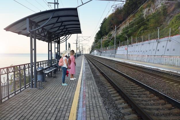 Várias pessoas esperam na plataforma ferroviária deserta pelo trem da manhã