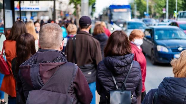 Várias pessoas esperando o transporte em uma estação, carros na estrada