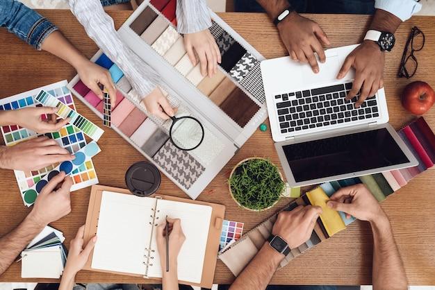 Várias pessoas estão sentadas sobre um laptop e amostras de cores.