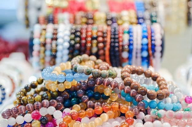 Várias pulseiras de pedras preciosas bonitas empilhadas à venda no mercado.