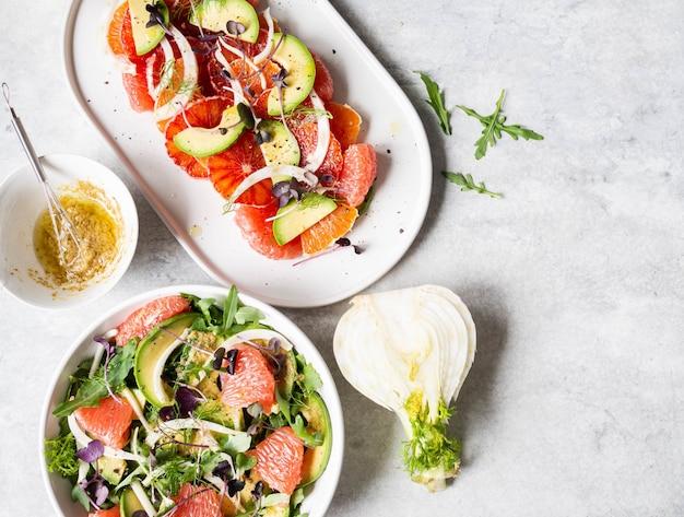Várias saladas de erva-doce com cítricos em cima da mesa