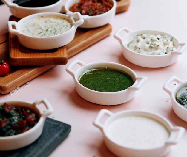 Várias saladas e sopas em cima da mesa