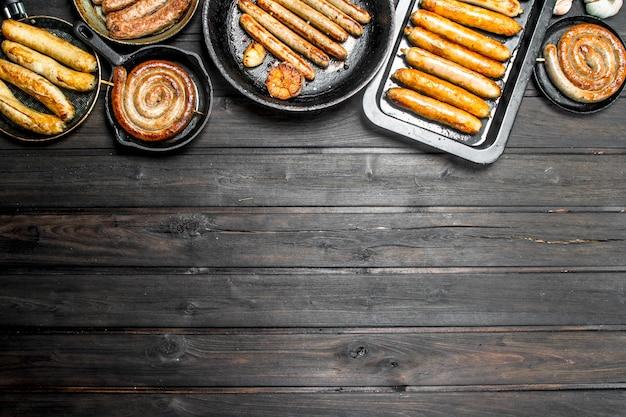 Várias salsichas fritas com ervas e especiarias na mesa rústica