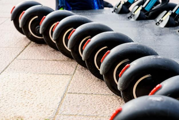 Várias scooters elétricas pretas estacionadas em fila, para alugar.