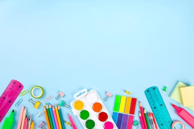 Várias secretarias de escola e materiais de pintura na parede azul. volta ao conceito de escola. vista do topo. copie o espaço