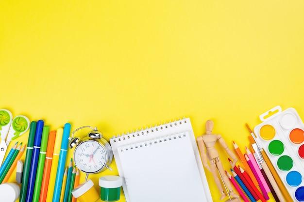 Várias secretarias escolares e suprimentos de pintura em fundo amarelo. volta ao conceito de escola.