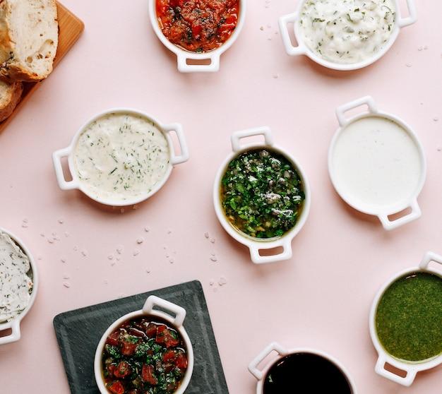 Várias sopas e saladas na mesa