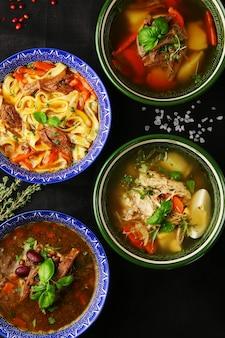 Várias sopas tradicionais com ingredientes vegetarianos orgânicos e utensílios de cozinha, vista superior.