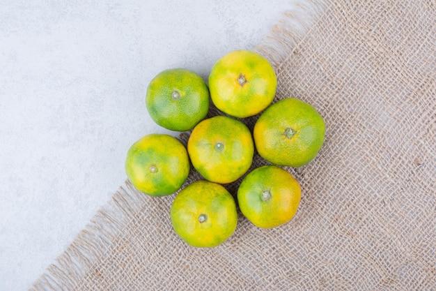 Várias tangerinas frescas e azedas em pano de saco. foto de alta qualidade