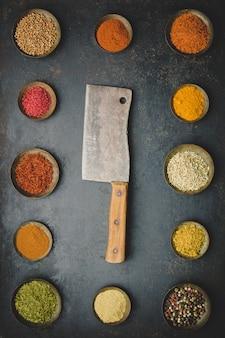 Várias tigelas de especiarias e faca de carne