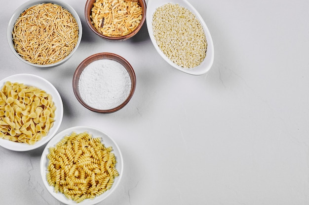 Várias tigelas de macarrão cru em branco com farinha.