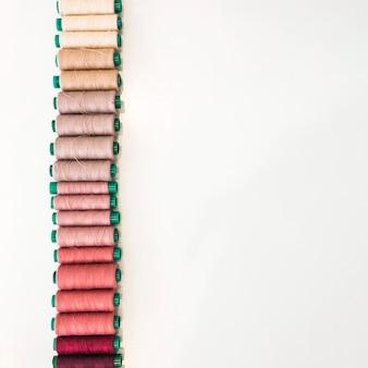 Várias tonalidades de bobinas dispostas em uma fileira no pano de fundo branco