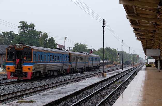 Várias unidades a diesel do trem local estão saindo da estação da cidade após receber o sinal verde, é permitido deixar a estação, linha norte da tailândia.