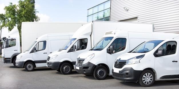 Várias vans e caminhões estacionados no estacionamento para alugar