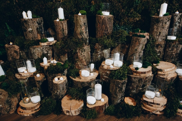 Várias velas em tocos de árvores para decoração de casamento