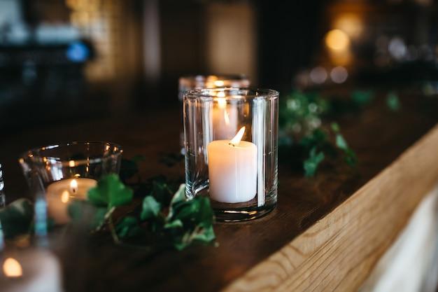 Várias velas estão na prateleira de madeira