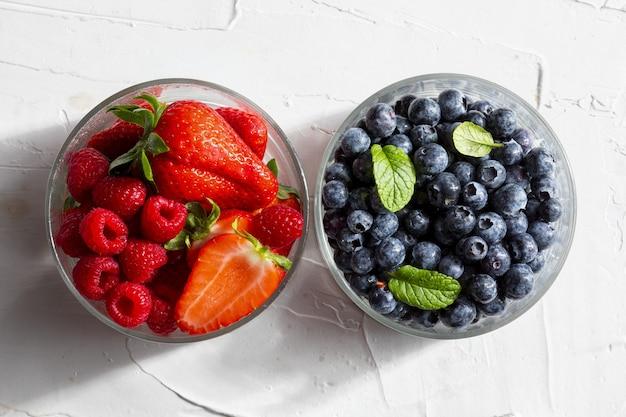 Variedade apetitosa de frutas da floresta morangos morangos grandes framboesas mirtilos bagas vermelhas em uma tigela de vidro e folhas de hortelã hortelã hortelã na superfície texturizada branca