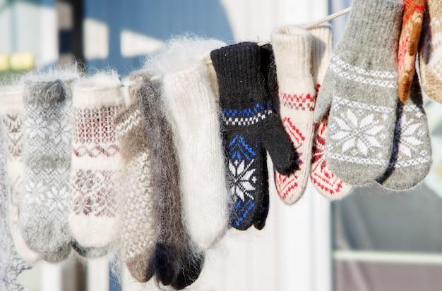 Variedade colorida de malha de luvas de lã, pendurado em uma corda
