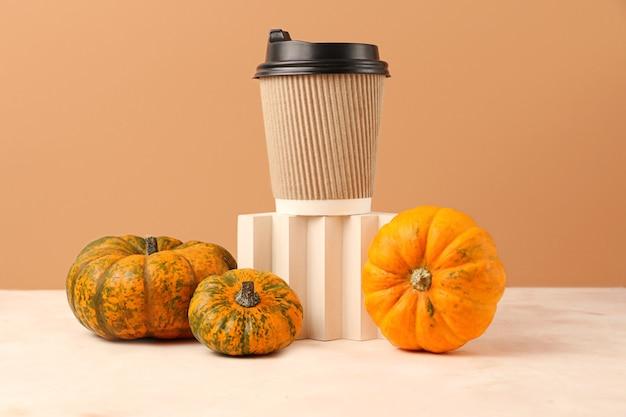 Variedade de abóboras perto do pódio geométrico com xícara de café artesanal