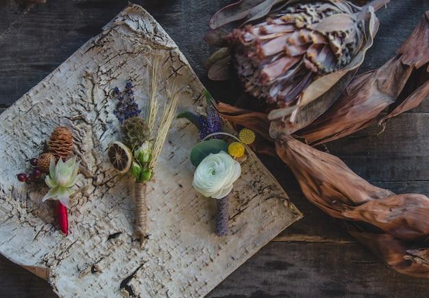 Variedade de alfinetes de jaqueta preparados com frutas secas e flores simbólicas sazonais em cima da mesa.
