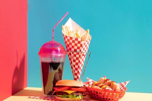 Variedade de alimentos com copo de suco e cheeseburger