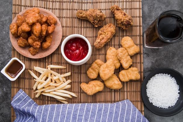 Variedade de alimentos de frango com batatas fritas e refrigerante na esteira de bambu