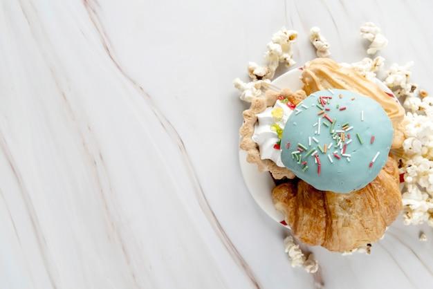 Variedade de alimentos doces no prato com pipocas sobre a superfície texturizada