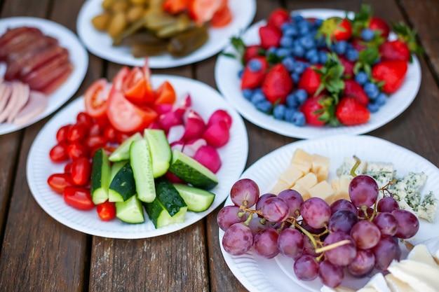Variedade de alimentos saudáveis e lanches em pratos de papel - frutas, vegetais, frutas vermelhas e queijo