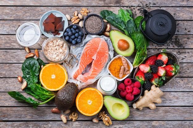 Variedade de alimentos saudáveis e saudáveis, ingredientes de superalimento para o estresse, ansiedade, fadiga crônica, alívio da depressão, redução e relaxamento na mesa da cozinha. vista superior do plano de fundo Foto Premium