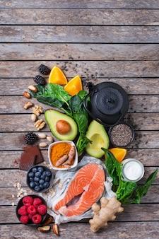 Variedade de alimentos saudáveis e saudáveis, ingredientes de superalimento para o estresse, ansiedade, fadiga crônica, alívio da depressão, redução e relaxamento na mesa da cozinha. vista superior do plano de fundo