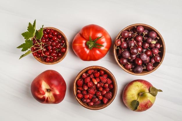 Variedade de alimentos vermelhos em um fundo branco, vista superior. frutas e vegetais contendo licopeno.