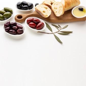 Variedade de alto ângulo de fatias de pão de azeitonas e azeite