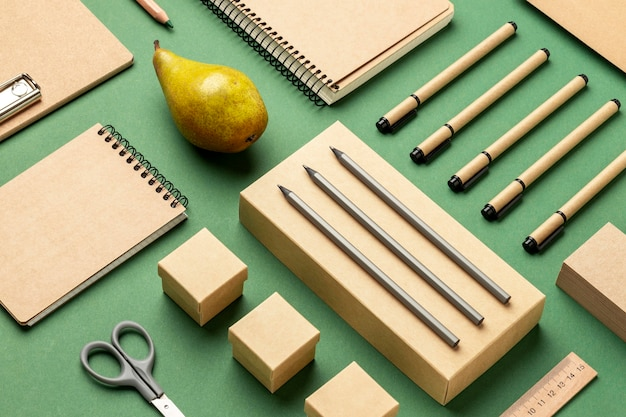 Variedade de ângulo alto com elementos de papelaria e frutas