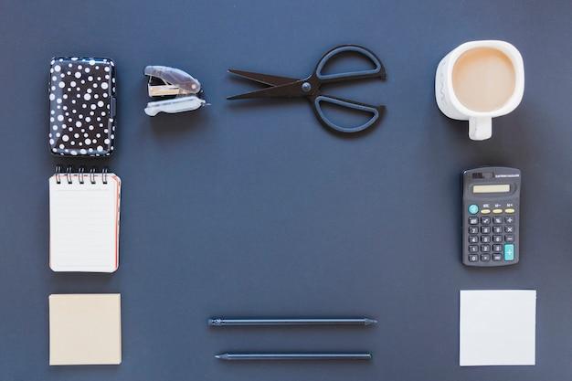Variedade de artigos de papelaria perto da xícara de café e calculadora